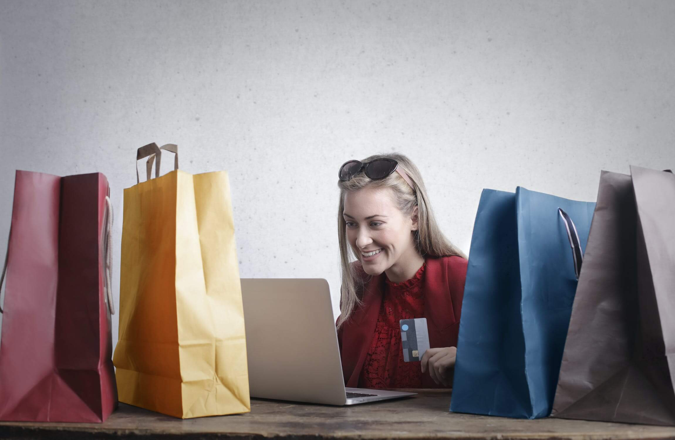A woman surrounded by bags, holding a credit card, looking at a laptop