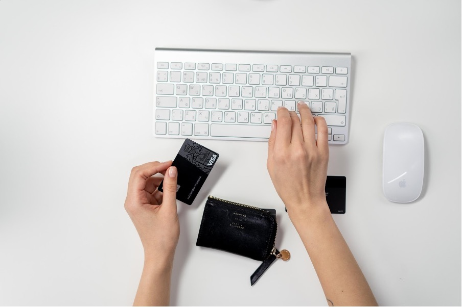 A hand holding a debit car while the other types on a keyboard