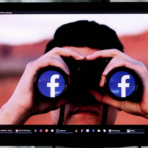 A man looking through a pair of binoculars with the facebook logo on them