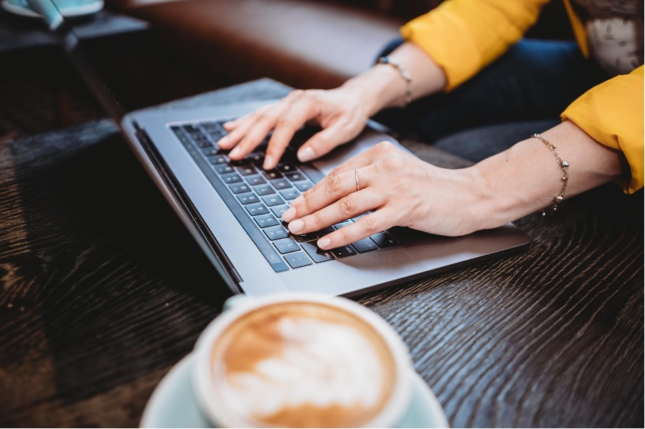 A woman typing on a laptop with a cappuccino next to them